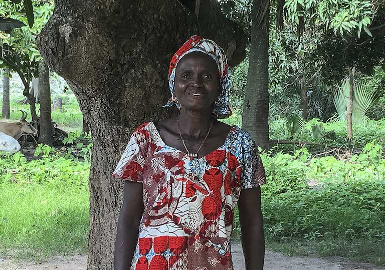 Aissatou Sambou, president of the Kawawana oyster collectors' association, stands in front of a tree by her home. Image by Jennifer O'Mahony for Mongabay.