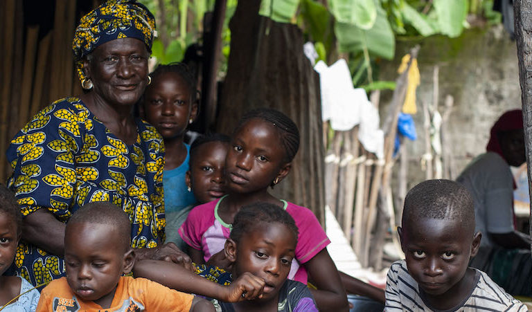 Dienaba Diedhiou, an oyster collector in her 70s, poses with her grandchildren. Image by Jennifer O'Mahony for Mongabay.