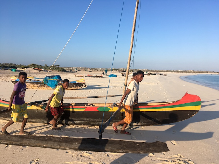 Fishermen in southwestern Madagascar carry a pirogue to the sea. Image by Rowan Moore Gerety for Mongabay.