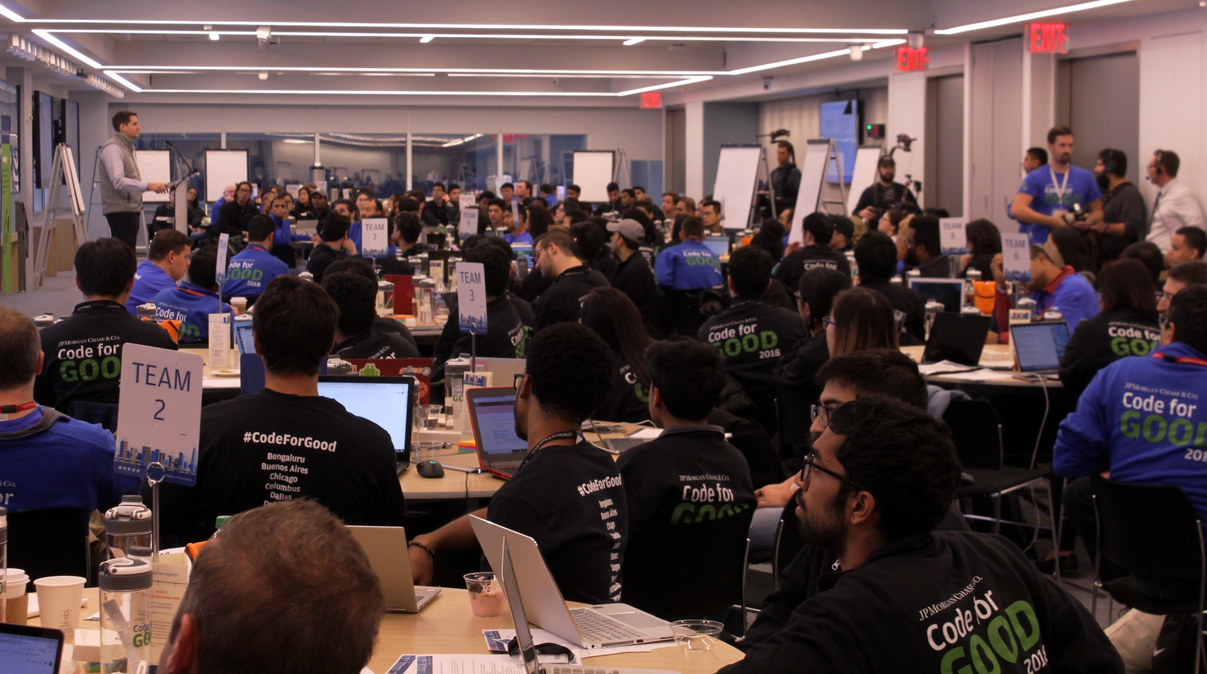 Student coders listen attentively during the Code for Good hackathon opening remarks.
