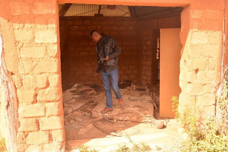 A Yiaku man inspects the damage to a recently built museum of Yiaku culture. Herders who invaded Mukogodo Forest in search of pasture last year used the museum as an encampment. Image courtesy of the Yiaku Laikipiak Trust.