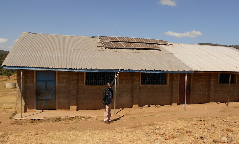 A Yiaku man points to solar panels atop a school where children are taught Yiaku language and culture. The Yiaku are working to preserve their traditional knowledge, which includes successful approaches to conserving Mukogodo Forest. to Image by Shadrack Kavilu for Mongabay.