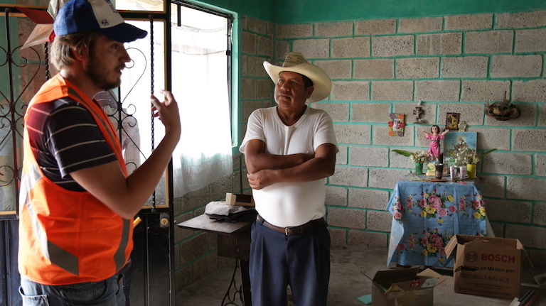 Javier Hernández, a member of ONergia, a solar power cooperative based in Puebla City, discusses home solar panel installations with a curious neighbor. Image by Ethan Bien for Mongabay.