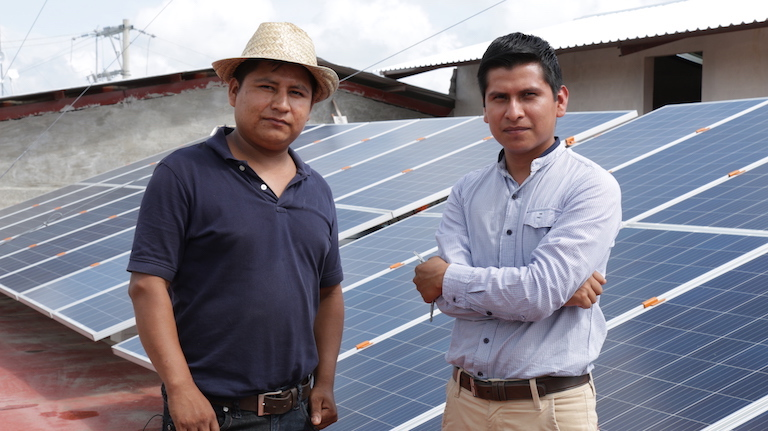 Nicasio Esteban, one of the Tosepan cooperative's team of young solar panel installers, and Ofelio Julian, who heads Tosepan's solar project and micro-finance collective, pose in front of a solar panel array on top of the cooperative's microfinance bank branch in Ayotoxco Guerrero, Puebla. Image by Ethan Bien for Mongabay.