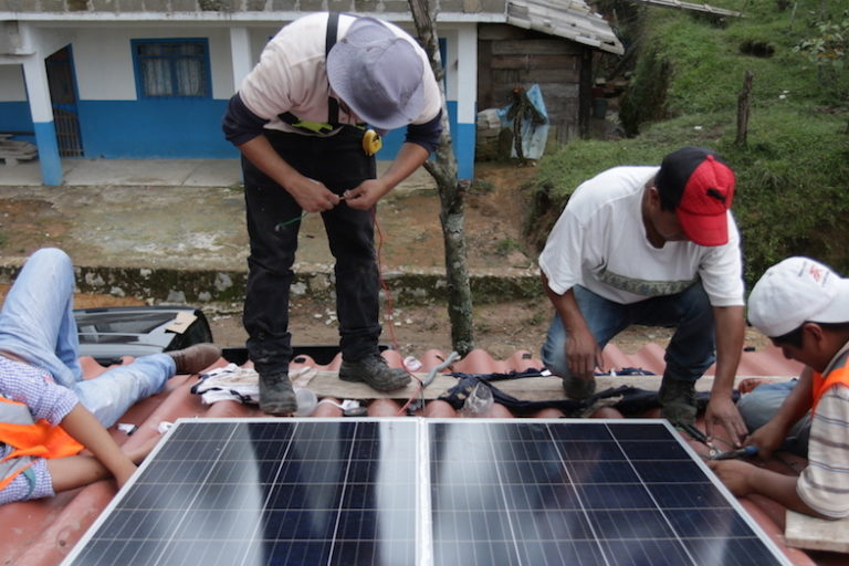 Members of the Tosepan cooperative's youth solar panel installation team and the ONergia solar cooperative put the finishing touches on a domestic panel installation while community members chip in. Image by Ethan Bien for Mongabay.