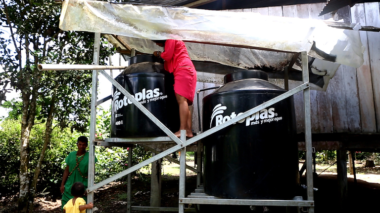 Flor Tungay inspects the filtration tank in a rainwater catchment system in her village of Aboquehuira in the Ecuadorean Amazon. Image by Dan Collyns for Mongabay.