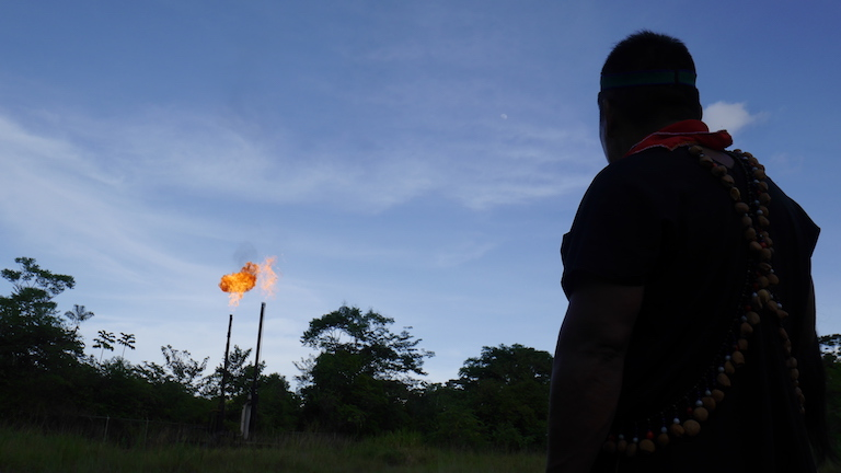 Emergildo Criollo looks on at a gas flare near an oil refinery some 20 miles from Lago Agrio, at dusk. The flares, a common sight in the region, burn off gas from piped oil. Image by Dan Collyns for Mongabay.