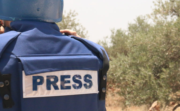 A journalist in a borrowed flak jacket and helmet works in Ni'lin, West Bank in June 2016. Photo by Genevieve Belmaker/Mongabay.