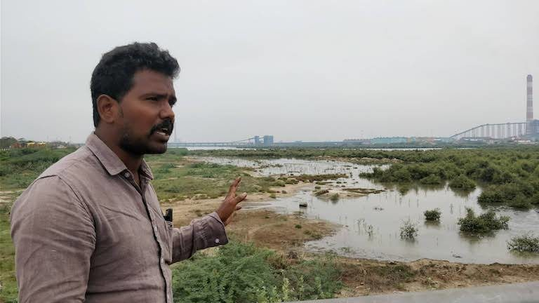 Saravanan points to a large salt pan, part of Ennore Creek in the city of Chennai. The nearby port's plan to convert the area into industrial real estate sparked protests among fishing communities in 2016. Image by Mahima Jain.