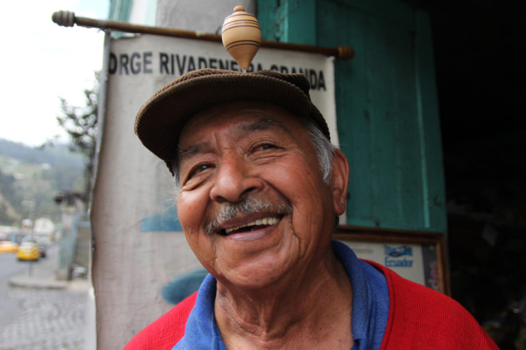 Jorge Rivadeneira Granda spins a top on his haed outside his shop in Quito, Ecuador. Photo by Kimberley Brown for Mongabay.