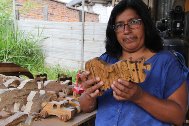 Susana Simbana holds a 3D puzzle of a cow, which she designed and made, while standing in front of more of her creations. Photo by Kimberley Brown for Mongabay.