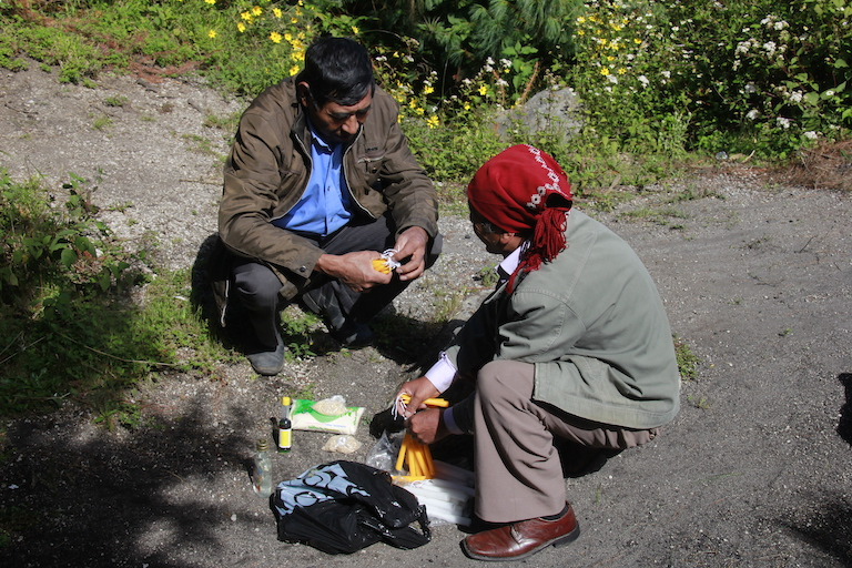 Marcelino Aguilar, head of Concepción Chiquirichapa's Department of Protected Areas, and Rumualdo López, a Maya spiritual guide and town councilmember, prepare materials for a Maya Mam fire ceremony on Siete Orejas. Image by Jorge Rodríguez for Mongabay.