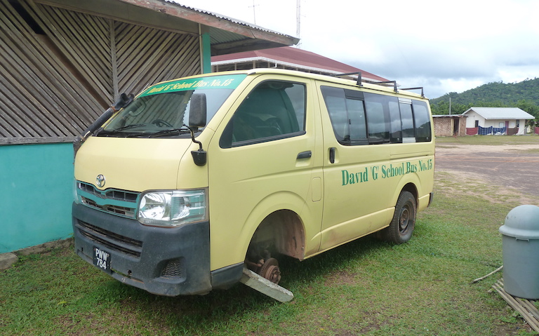 "A David ""G"" School Bus, one of a national fleet named for Guyana's president, David Granger, awaits repair on the center's grounds. Image by Carinya Sharples for Mongabay."