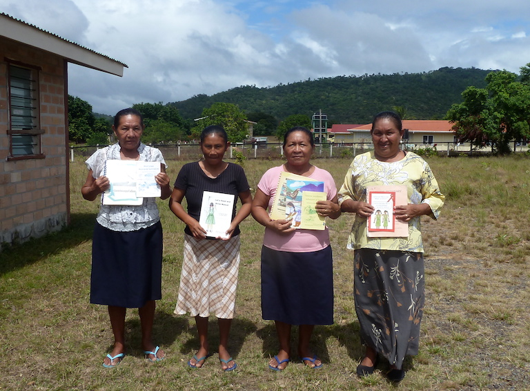 Four members of a local group called the Makushi Research Unit hold copies of books they have published. Coordinator Paulette Allicock, far right, teaches the Makushi language to Youth Learning Centre students. Image by Carinya Sharples for Mongabay.