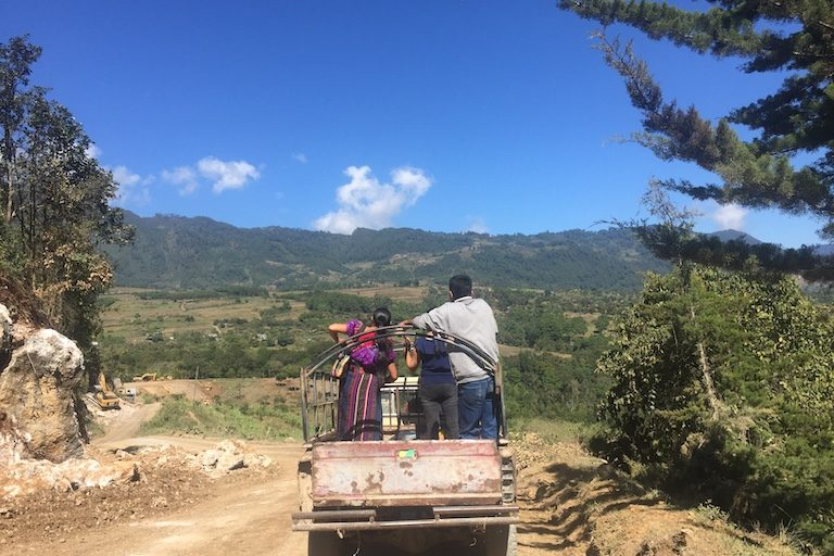 . Residents living near Cerro Amay catch a ride in a passing truck. Image by Max Radwin for Mongabay.