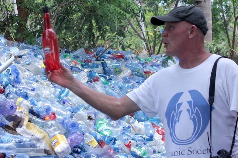 Steve Trott, director of Ecoworld, the Watamu Marine Association's plastic recycling project, holds a discarded bottle at the organization's collection yard. Image by Anthony Langat for Mongabay.