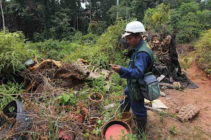 Environmental monitor Elmer Hualinga examines waste discarded near the city of Nuevo Andoas in Block 192. Image © Barbara Fraser.