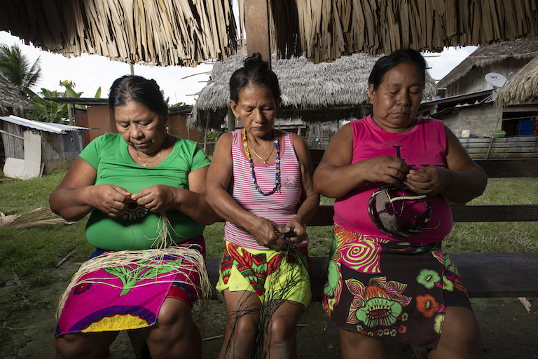 Three Emberá women weave masks and dishes of natural fibers. Image by Alexander Arosemena for Mongabay.