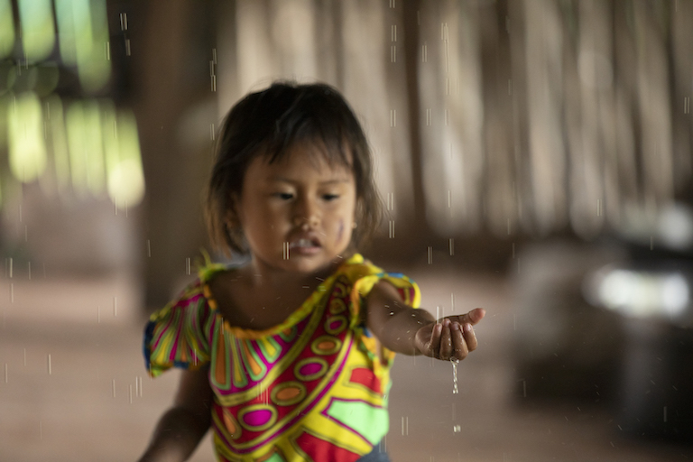 A girl plays with water during one of the many rains that fall in the Darién throughout the year. Image by Alexander Arosemena for Mongabay.