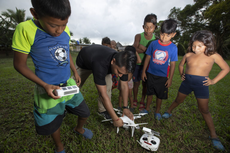 Carlos Doviaza readies his drone for takeoff in the community of Puerto Indio. Every time Doviaza flies his drones, children come to watch. Image by Alexander Arosemena for Mongabay.