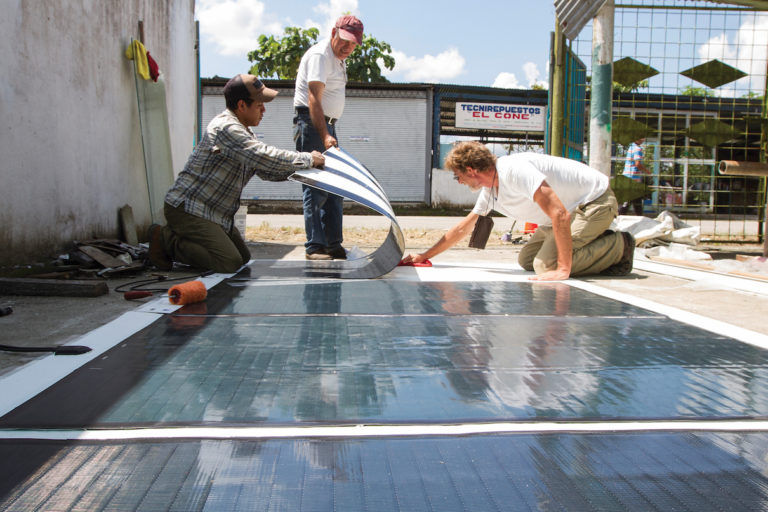 Peter May, right, the solar boats' designer, prepares Tapiatpia's solar panels with his team. Image by Fundación Kara Solar.