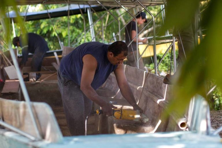 Builders work on the first solar canoe's fiberglass body. Image by Fundación Kara Solar.