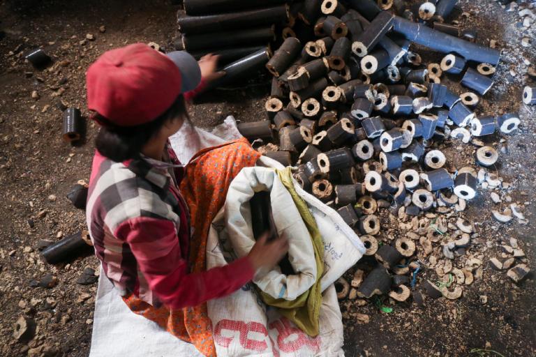 A worker sorts rice husk bricks. Photo by Victoria Milko.