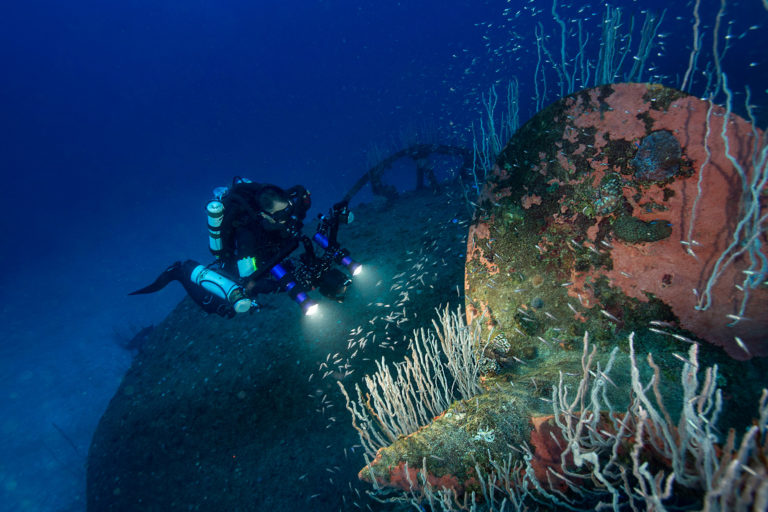 Greg Asner photographing corals growing on the Nagato. Photo by Rick Miskiv / 22degrees.co