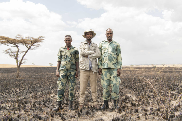 Ashagre Gemeda (l) and Hirpha Badeso (r), poses for a portrait with Chief warden Desta Bedaso at the Senekele Swayne's Hartebeest Sanctuary. Photo by Maheder Haileselassie Tadese.
