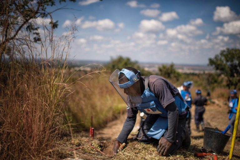 clearing mines in Angola, a HALO Trust worker wearing blue protective gear on his knees probing grass and dirt with his hands. Credit: The HALO Trust