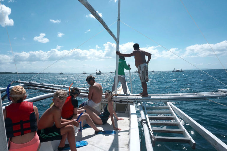 A tourist boat in Donsol joins several others in search of whale sharks. Image by Nina Unlay.