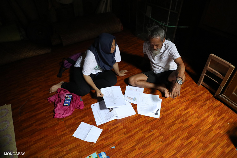 Aseanty going over community documents and historical records with Bandi at Sungai Utik. Photo by Rhett A. Butler