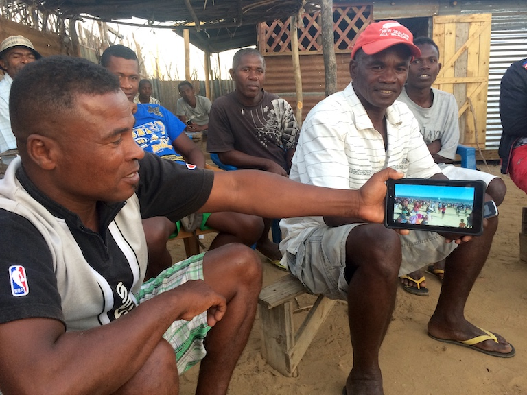 Gano (in red cap), a member of Zanadriake, an organization of fishers and divers that opposes Base Resources's plan to build a small port at the beach near Toliara, looks on as his friend Gentsy shows a video of the beach during a crowded holiday. Image by Edward Carver for Mongabay.