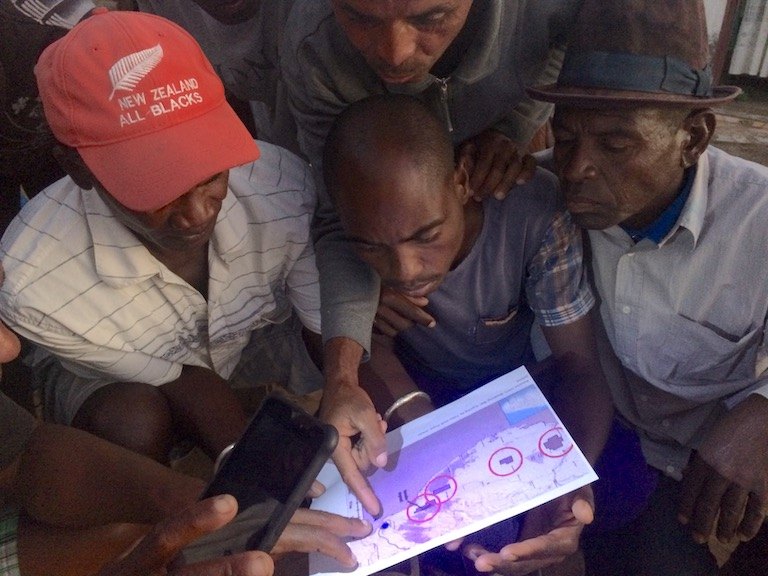Gano (in red cap) and other members of Zanadriake look at a map of Base Resources's concessions in the region. One man points at the blue dot that represents Toliara, the city where many of the group's members live, and where the company is planning to build a small port that they object to. The company plans to begin construction on the concession nearest to Toliara this year. Image by Edward Carver for Mongabay.