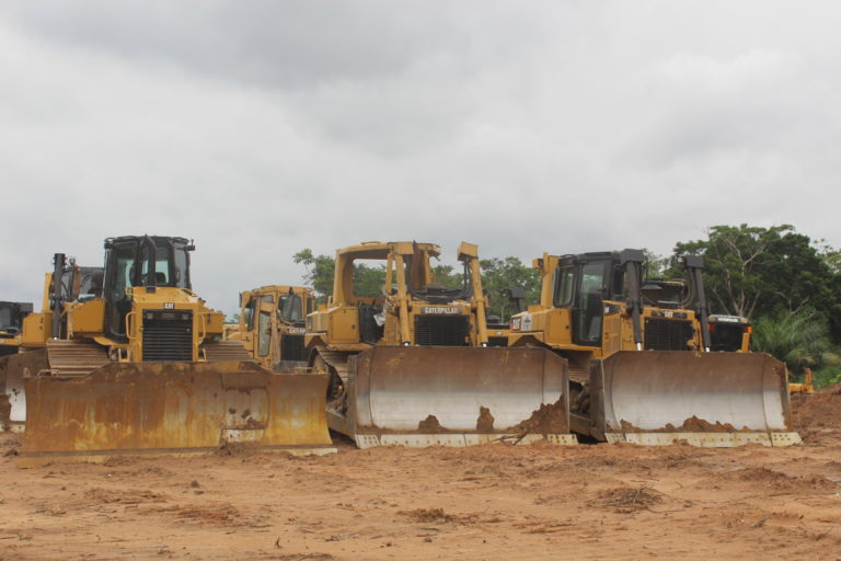 Bulldozers parked in a muddy clearing near near Okuni, Cross River State, Nigeria