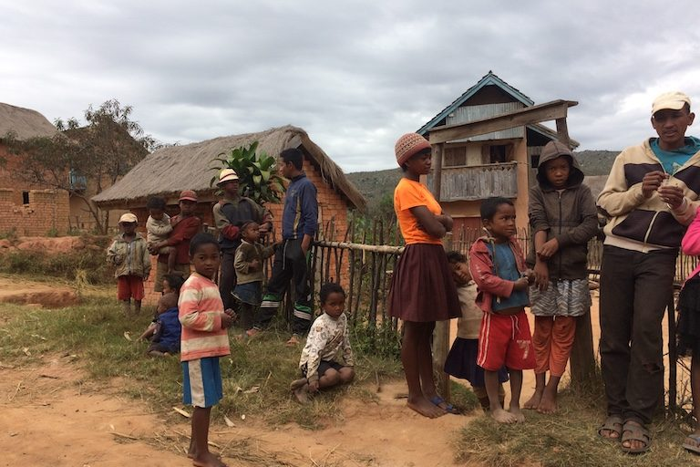 "François Rakotonirina (far right), encouraged a Mongabay reporter to take as many photographs of his village as possible. ""Show them everything we have here,"" he said. ""Our rice fields, our houses, all the things we don't want to give up."" Image by Edward Carver for Mongabay."