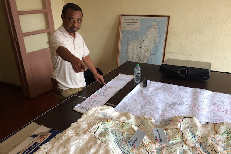 Kotandrajaona Rajoelisolo, general secretary of BIMTT, a civil society group, shows off a 3D map of the Sahanivotry area that his group built based on data obtained from the national geography and hydrographic institute (FTM). Image by Edward Carver for Mongabay.