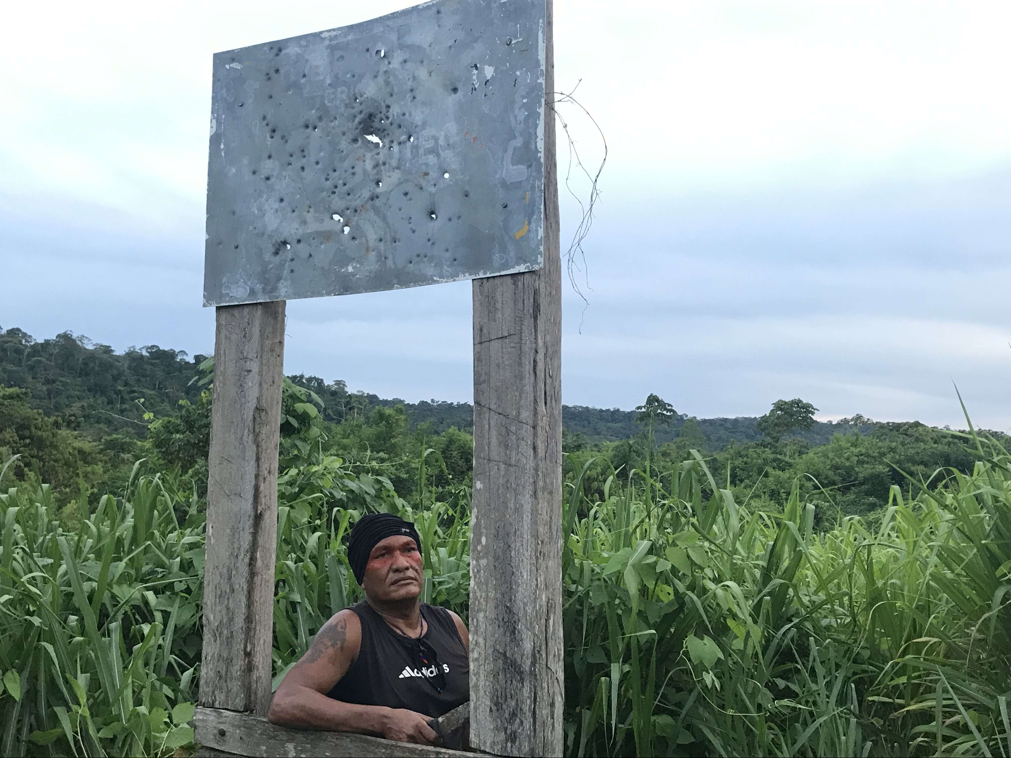 "Olímpio Iwyramu Guajajara, the leader of the ""Guardians of the Forest,"" poses for a photo in front of the Arariboia sign that is all engraved by bullet marks, in Maranhão state, on Jan 30, 2019. Image by Karla Mendes/Mongabay"