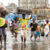 Beira residents carrying belongings wade through flooded street in Beira.