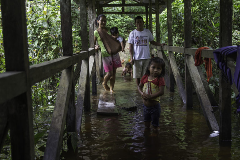 Community members stand on the only bridge that leads to their home that was flooded by winter rains in the community of Llanchama, in Ecuador's Yasuni National Park. Photo by Kimberley Brown for Mongabay.