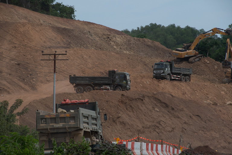 Trucks cart away fill dirt from a hilltop for the highway's construction. Image by John C. Cannon/Mongabay.