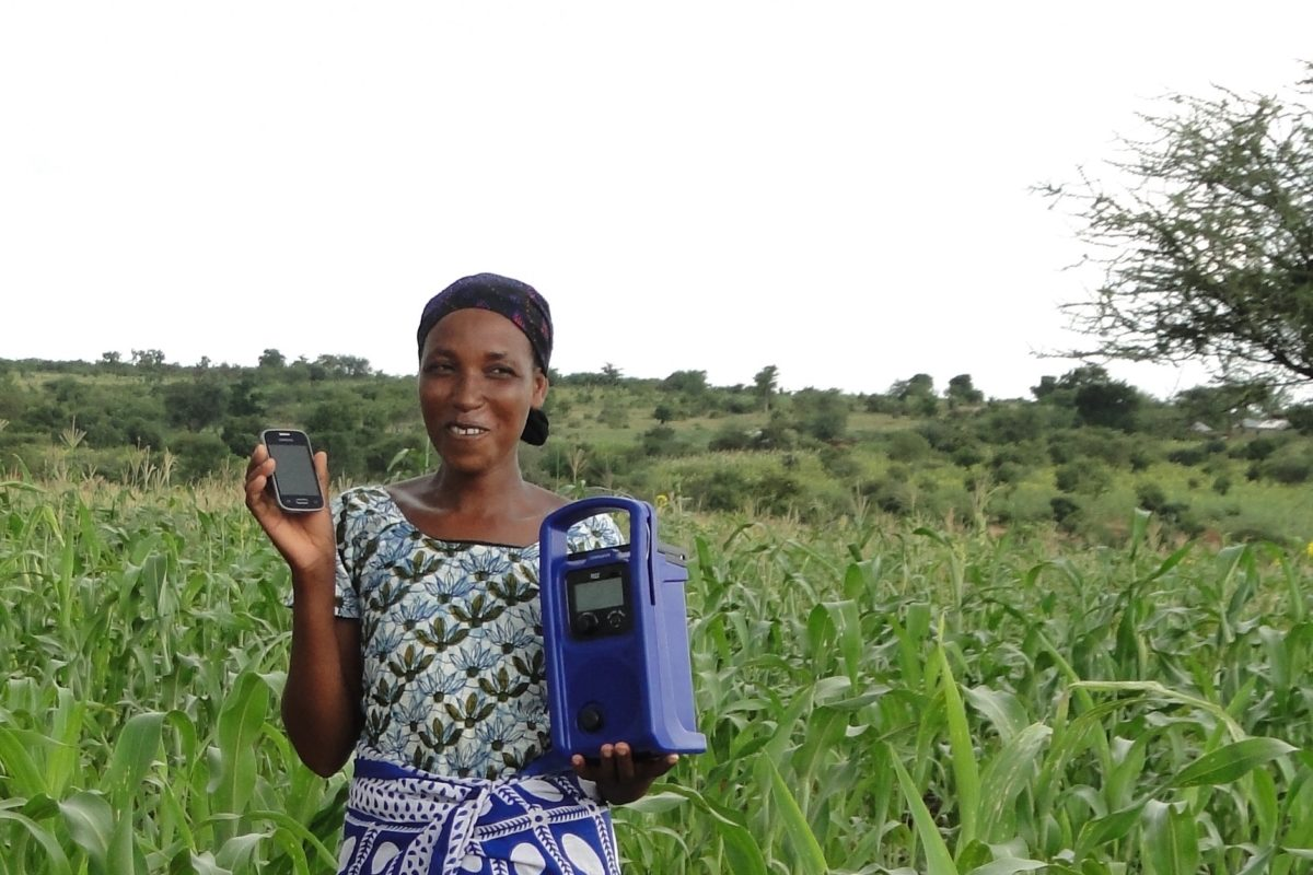 Tanzanian farmer Julia Yusufu with two of her agricultural tools, a radio and her cell phone. Image courtesy Farm Radio International