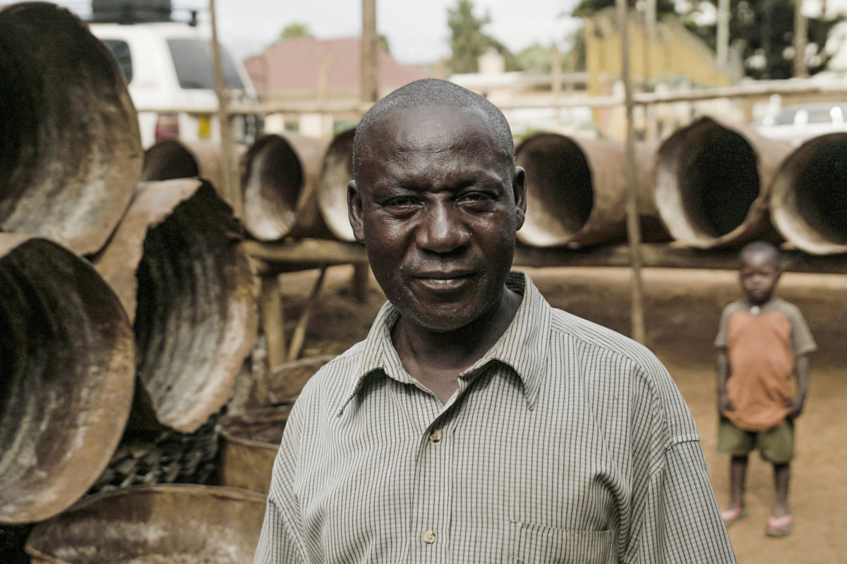 John Mulindwa in front of drums for capturing nsenene. Image by Thomas Lewton for Mongabay.