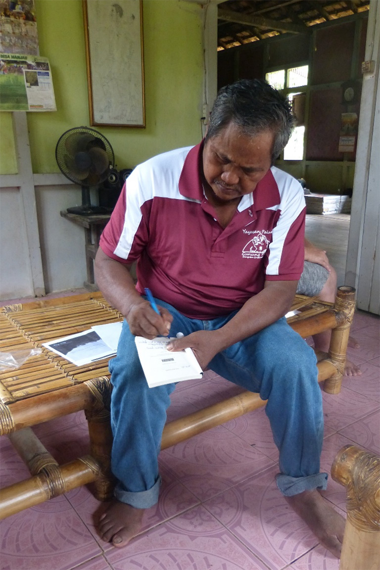 Yohanes Terang writing his poetry in his Manjau home. © Douglas Sheil