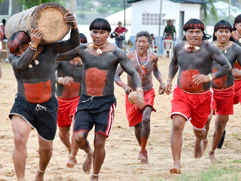 Xavante men participating in a traditional log race. The rapid spread of COVID-19 could jeopardize the future of indigenous communities throughout the Brazilian Amazon rainforest and Cerrado savanna. Photo credit: Edson Bueno / FUNAI
