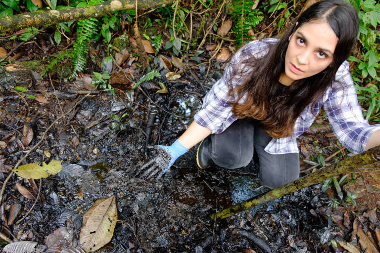 In the Pozo Aguarico region of Ecuador, lawyer Maria Cecilia Herrera shows the oil pollution that remains in the ground 30 years after oil production ceased. Photograph by Enrico Aviles, 2020.