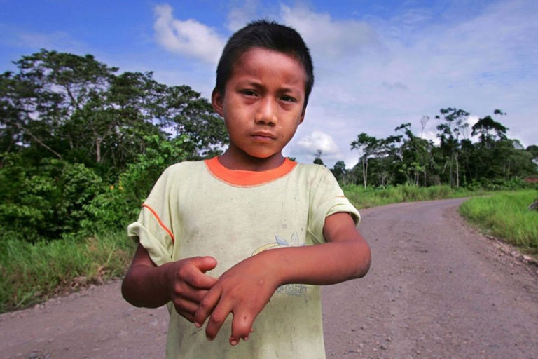 Nine-year-old, Jairo Yumbo, stands on the road in front of his home in the village of Rumipamba.