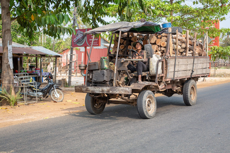 Trucks packed full of freshly cut logs trundle down a main highway out of a Cambodian wildlife sanctuary. Photo by Chris Humphrey for Mongabay.