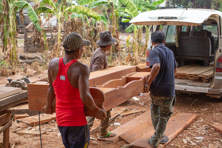 Workers load wooden furniture into a van. Photo by Chris Humphrey for Mongabay.