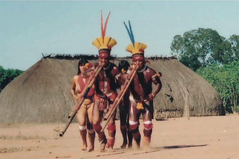 Flute players announcing a kuarup in front of a Xinguano maloca (communal hut). Photo courtesy of Noel Villas Boas